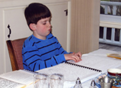 Photo Caption: Jack, age 9, reading from a Braille text