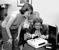 Photo Caption: A JBI subscriber is shown how to use her free Talking Book playback machine.