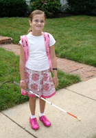 Photo Caption:  Madeline, ready for her first day of school, with JBI customized Braille textbooks in hand
